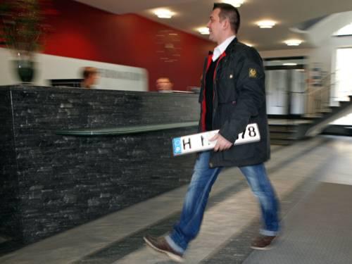 Ein Mann geht mit einem Kfz-Kennzeichen in der Hand zum Bürgerbüro der Region Hannover im Regionshaus an der Hildesheimer Straße in Hannover.