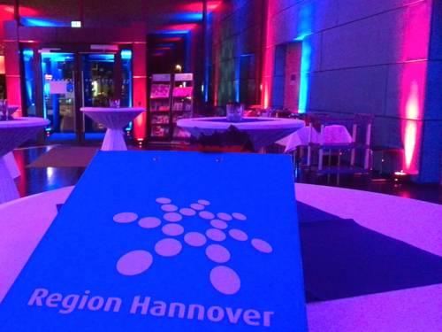 Stehtische stehen im Foyer des Regionshauses, Eingang Hildesheimer Str. 18. Scheinwerfer lassen den Raum in den Farben Rot und Blau leuchten.
