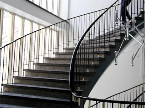 Ein modernes Treppenhaus, in dem eine Person gerade die Stufen runterläuft. Von der Person sind nur die Beine zu sehen.