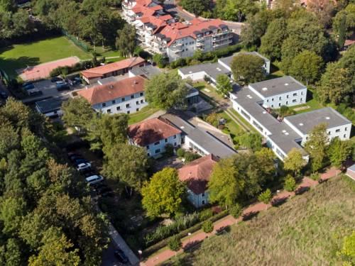 Luftaufnahme eines Gebäudekomplexes, auf dem Außengelände sind Spiel- und Sportgeräte.