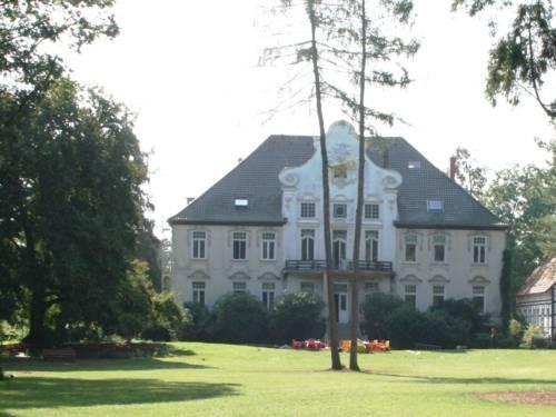 Blick über eine gepflegte Rasenfläche auf das Hauptgebäude des KulturGutes Poggenhagen.