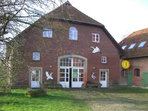 Älteres Backsteingebäude mit angrenzender Stallung. An der Fassade sind Bilder von Reihern und einer Sonne befestigt