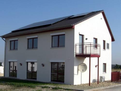 Einfamilienhaus mit weißer Fassade, großen Fenstern und einem Balkon. Auf dem Dach ist eine Solaranlage, Photovoltaikzellen erzeugen Strom, Solarthermie sorgt für Wärme.