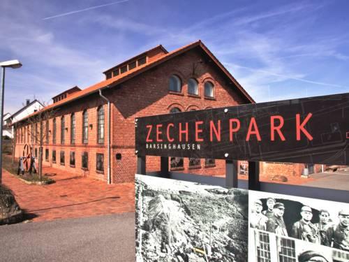 """Schild mit der Aufschrift """"Zechenpark. Barsinghausen"""", dahinter ist ein Backsteingebäude."""