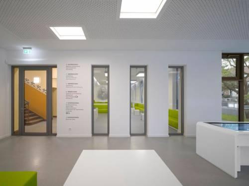 Ein Foyer mit einem Medientisch. Rechts neben der Tür, die in ein Treppenhaus und zu weiteren Räumlichkeiten führt, ist an die Wand geschrieben, was in den einzelnen Stockwerken zu finden ist.
