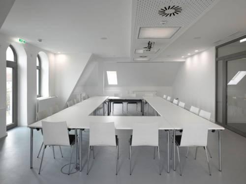 Ein Seminarraum mit neunzehn Stühlen an zusammengestellten Tischen.