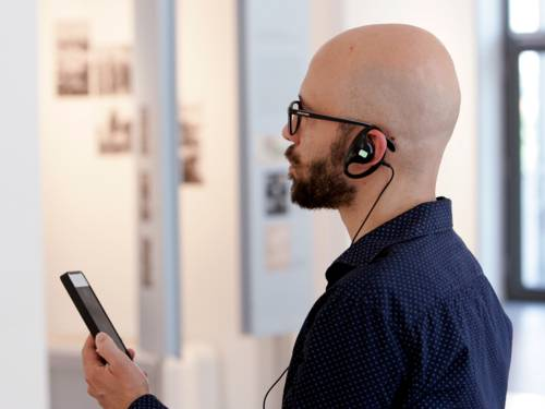 Ein Mann mit Bart und Brille steht mit einem Smartphone in der Hand und Kopfhörern im Ohr in einem hellen Raum