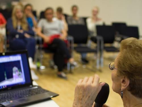 Zeitzeugin Henny Simon hält einen Vortrag. Sie sitzt auf einem Stuhl und hält ein Mikrofon in der Hand. Vor ihr ist ein Laptop aufgebaut.