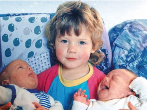 Kleineres Kind mit zwei Babies links und rechts im Arm