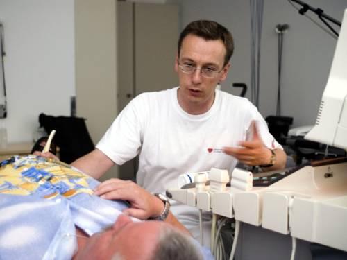 Ein Mann fährt mit einem Ultraschallkopf über den Unterleib eines liegenden, älteren Mannes.
