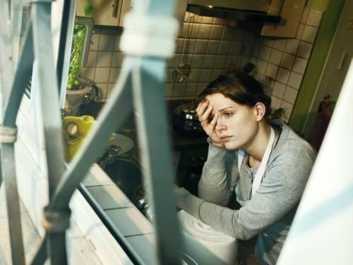 Eine Frau schaut mit leerem Blick aus einem Küchenfenster. Das Fenster ist von außen vergittert.
