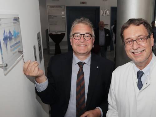 Zwei Männer mit Brille und Krawatte, einer im Anzug, einer im Arztkittel. Beide freuen sich sichtbar über ein neues Schild an der Innenwand.