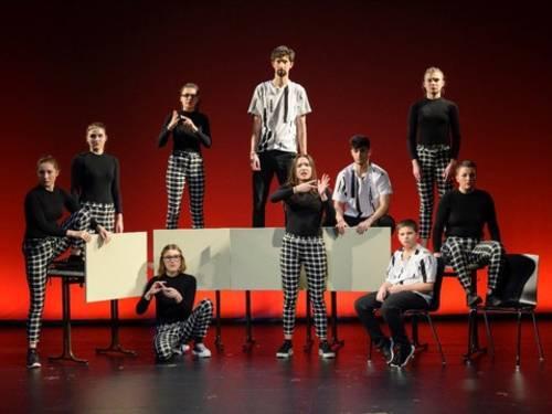 Junge Menschen auf einer Bühne vor einem rot beleuchteten Hintergrund