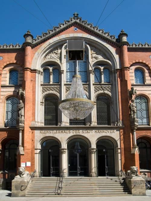 Zu sehen sind ein großer Kronleuchter in der Mitte der Straße und der Eingang zum Künstlerhaus.