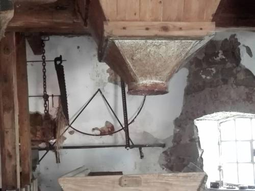 Zeigt den Mahltrichter, in den die Getreidekörner vor dem Mahlvorgang fallen. Der Mahltrichter führt die Körner in den Mahlvorgang ein. In der Mitte des Bildes ist ein Abspielsymbol abgebildet.