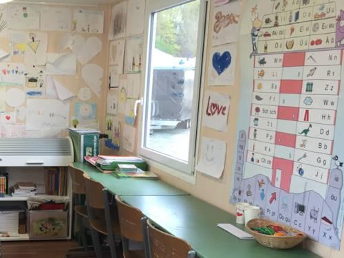 Der Schulwagen von Innen mit Tischen und Stühlen. Die Wände sind beklebt mit Zeichnungen, Bastelarbeiten und Unterrichtsmaterialien.