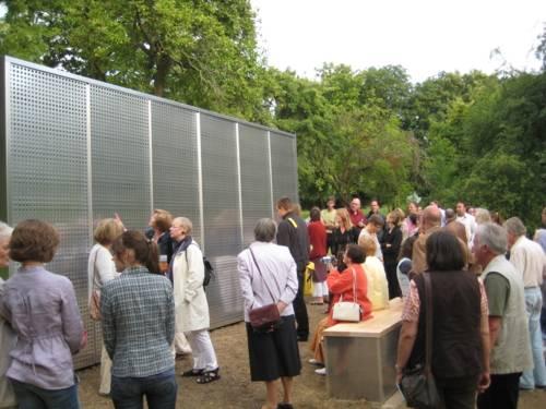 Menschen vor einer großen Wand aus Metall