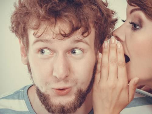Eine Frau flüstert einem jungen Mann mit Locken und Bart etwas ins Ohr.
