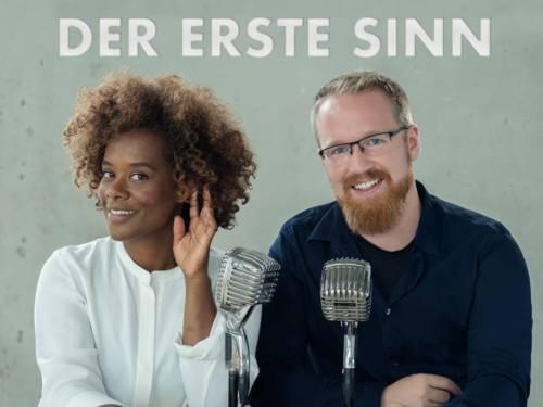 Eine Frau mit Locken und ein Mann mit Bart und zwei Mikrofone im Vordergrund.
