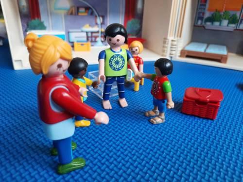 Situation mit Spielfiguren: Mann, Frau und zwei Kinder greifen sich an den Händen.