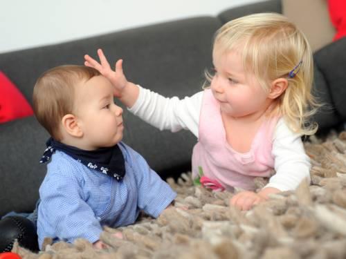 Zwei kleine Kinder auf einem Teppich beim Spielen