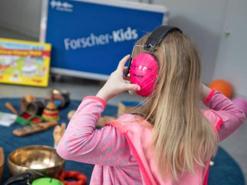 Ein Mädchen trägt Kopfhörer, im Hintergrund ist die Entdeckerkiste der Forscherkids zum Thema Klänge und Geräusche zu sehen, Instrumente und andere klingende Gegenstände oder Material für Hör-Experimente liegt daneben.