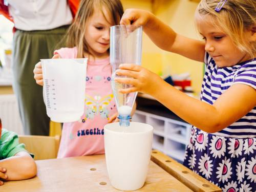 Zwei Mädchen füllen Wasser und Pulver mit Hilfe von Messbechern in einen Becher
