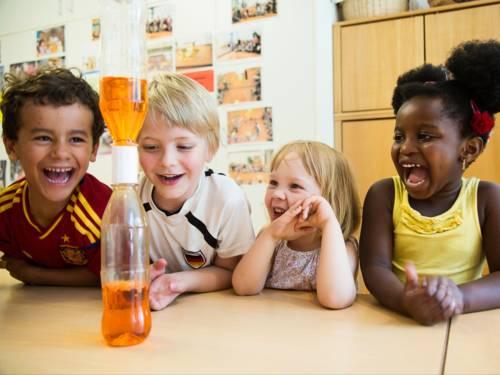 Forschen: Zwei Jungen und zwei Mädchen beobachten ein Experiment mit einer Flasche und Flüssigkeiten.