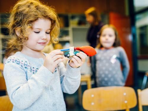 Ein Mädchen hält in ihren Händen ein Spielzeugauto und schaut es sich an. An dem Auto ist ein Luftballon befestigt, der Luft durch einen Strohhalm entgegen der Fahrtrichtung ausströmen lässt und so das Spielzeugauto fahreen lässt.