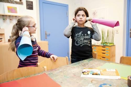 Zwei Kinder, die sich zusammengerolltes Papier an die Ohren halten um besser zu hören
