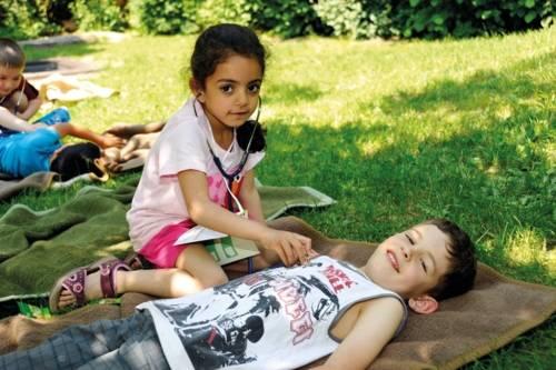 Kinder im Park, die sich gegenseitig mit einem Stethoskop abhören.