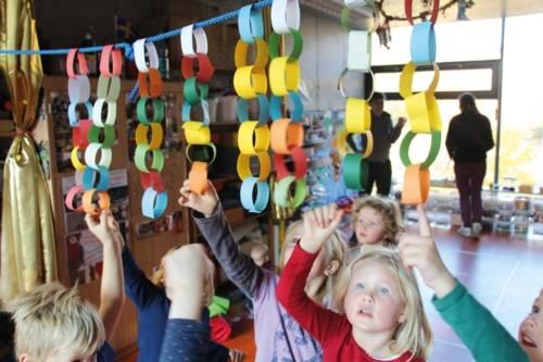 Kinder, nach farbigen Ringen greifen, die an einer durch einen Raum gespannten Leine hängen.
