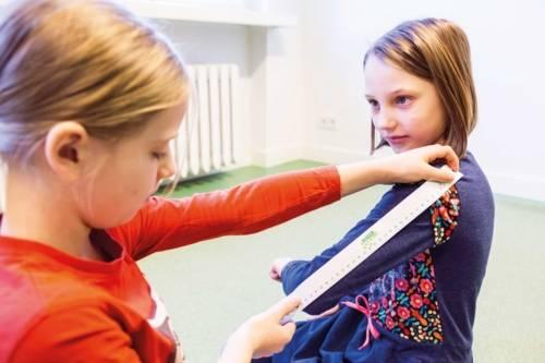 Zwei Mädchen, von denen eine die Oberarmlänge der anderen mit einem Lineal abmisst.