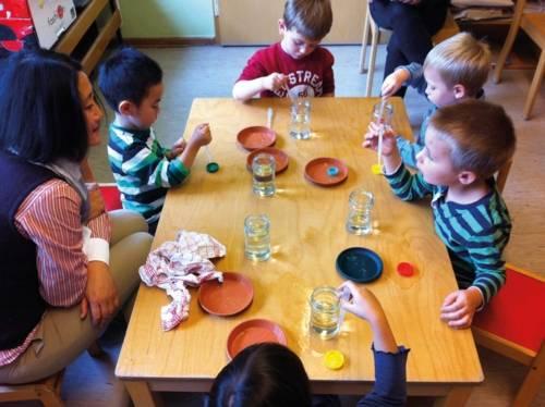 Kinder experimentieren mit Pipetten und Wasser