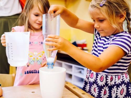 Zwei Mädchen experimentieren mit Wasser, einer aufgeschnittenen Plastikflasche und weiteren Gefäßen.