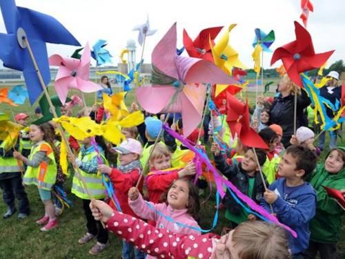 Kinder halten im Freien kleine Propeller in den Wind.