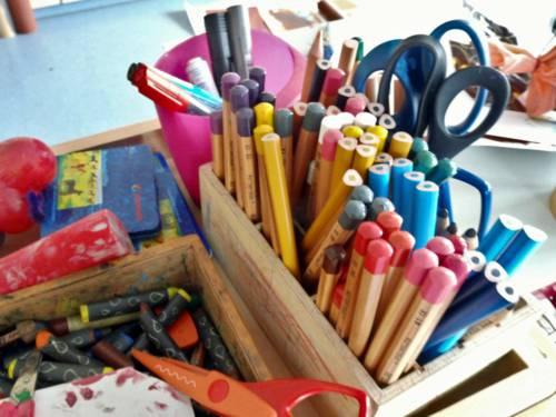 Stifte, Scheren und weiteres Material sind in einer kleinen Holzkiste.
