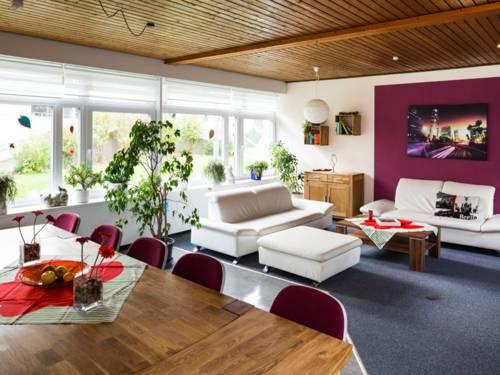 Ein Raum ausgestattet mit zwei weißen Sofas, einem Holzcouchtisch, einem kleinen Kommodenschrank, ein großen Esstisch mit rot gepolsterten Stühlen an der einen Tischseite, zwei kleinen Bücherregalem und einem großen Bild an der Wand sowie mehreren Grünpflanzen.