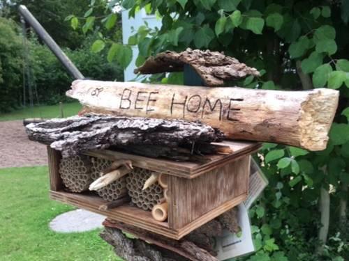 """Ein Insektenhotel aus unterschiedlichsten Materialien hat den Namen """"Bee Home"""" eingeritzt."""