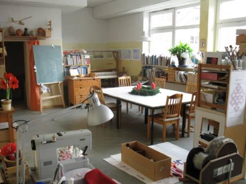 Mitten in einem Raum steht ein großer Tisch mit sechs Holzstühlen dran. In dem Raum befinden sich eine Tafel, Regale mit Bücher, eine Nähmaschine und viele Bastel- und Hobbyutensilien.