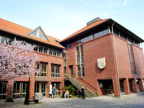 Großer Backsteinbau mit vielen Fenstern. Der blühende Kirschbaum lässt vermuten, dass das Bild im Frühjahr aufgenommen wurde.