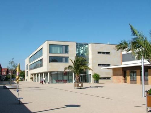 Rathaus und Rathausplatz der Stadt Hemmingen: Vor einem sommerlich blauen Himmel steht ein modernes Gebäude mit Flachdach und großen Glasflächen.