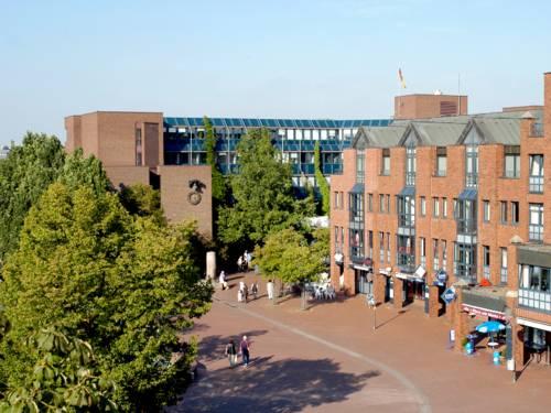 Ein Marktplatz mit Menschen, dahinter der rote Backsteinbau des Rathauses Langenhagen. Rechts ist das City Center Langenhagen zu sehen, links ein großer Baum.