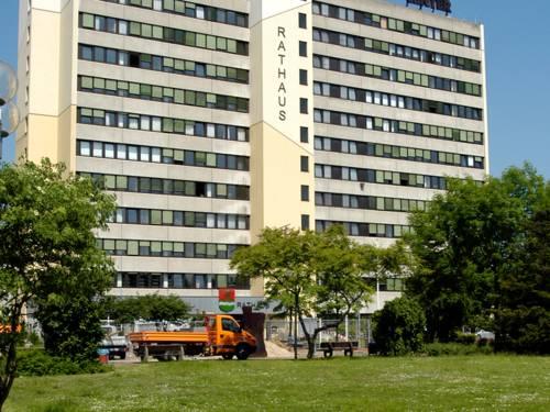Grünflache, im Hintergrund zwei Hochhäuser vor den ein oranger LKW parkt
