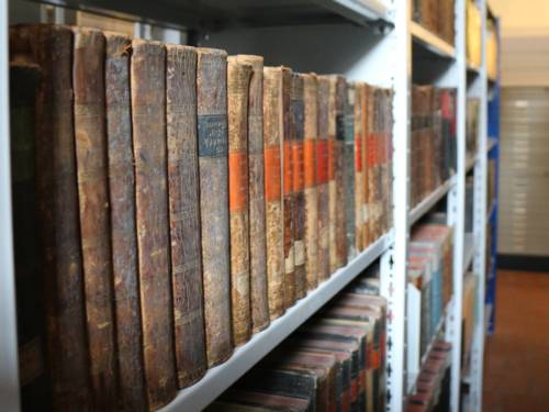 Ein Regal mit sehr alten Büchern links im Bild.