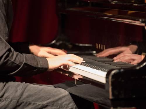 Die Hände eines Mannes, der Klavier spielt.