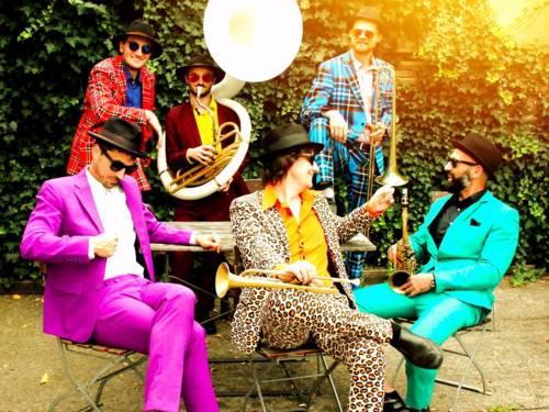 Sechs Musiker tragen farbenfrohe Kleidung und sitzen mit den Instrumenten auf Gartsnstühlen oder stehen im Grünen.