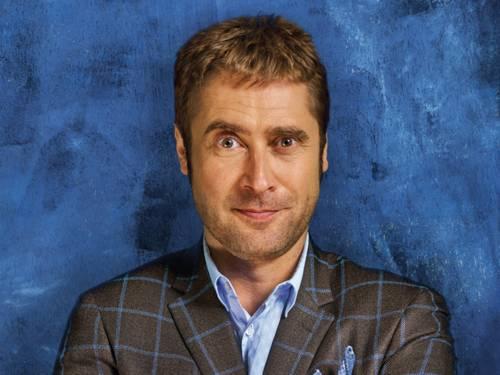 Porträtfoto eines Mannes vor blauem Hintergrund.