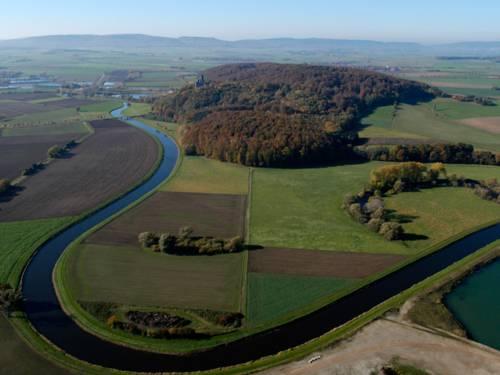 Mäandernder Fluss mit Feldern und Wiesen im Hintergrund Höhenzüge