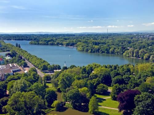 Die Wasserfläche des Maschsees ist von grünen Bäumen umgeben, der Himmel leuchtet blau.